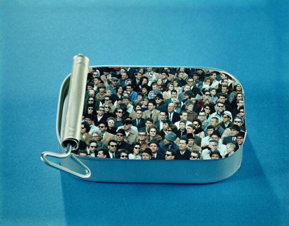 UNITED STATES - CIRCA 1960s:  Crowd of men and women packed inside open sardine tin.  (Photo by H. Armstrong Roberts/Retrofile/Getty Images)